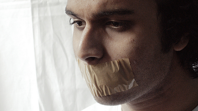 A man with a piece of tape over his mouth
