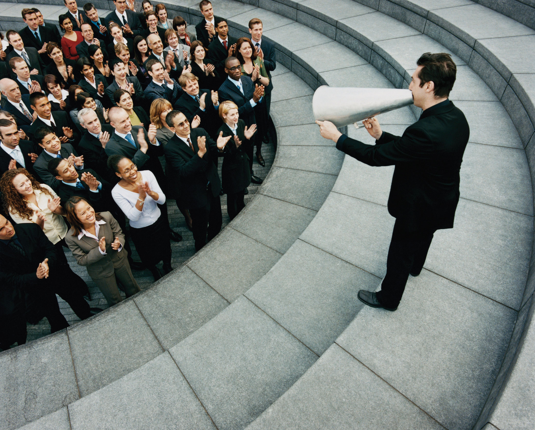 A crowd applauding a man using a cone to amplify his voice