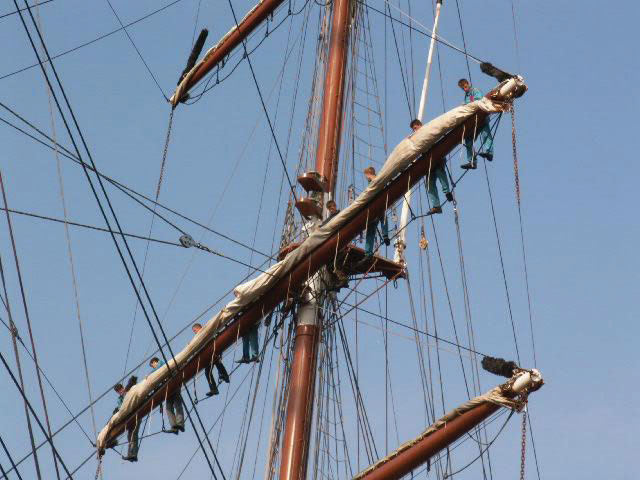 People standing on a ship's rigging